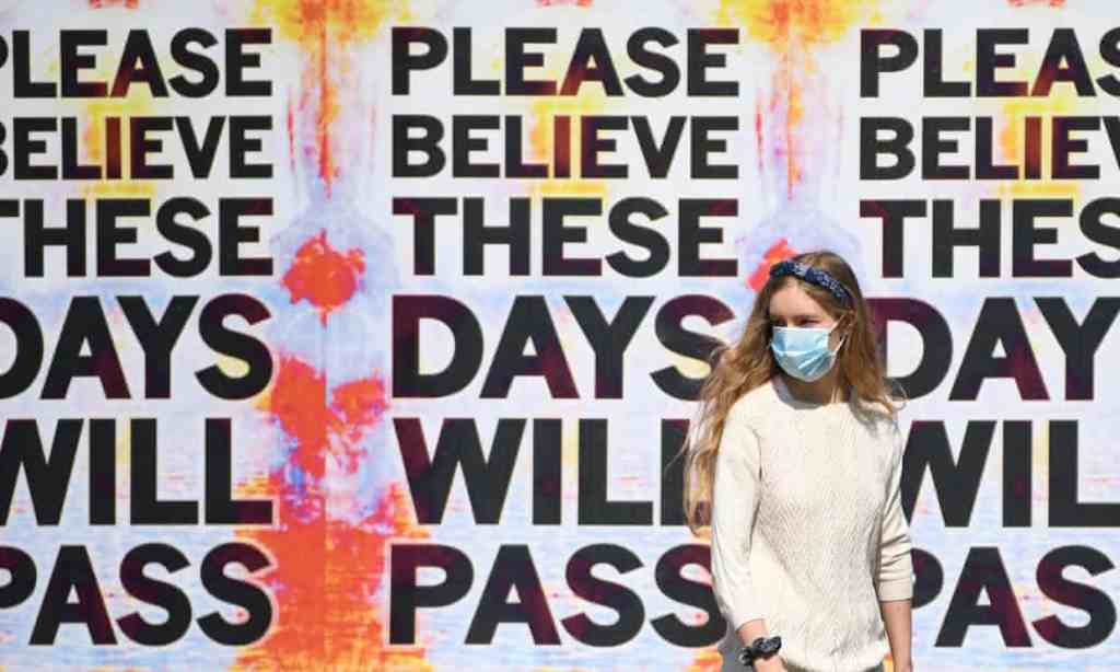 Woman in mask in front of poster saying These Days Will Pass